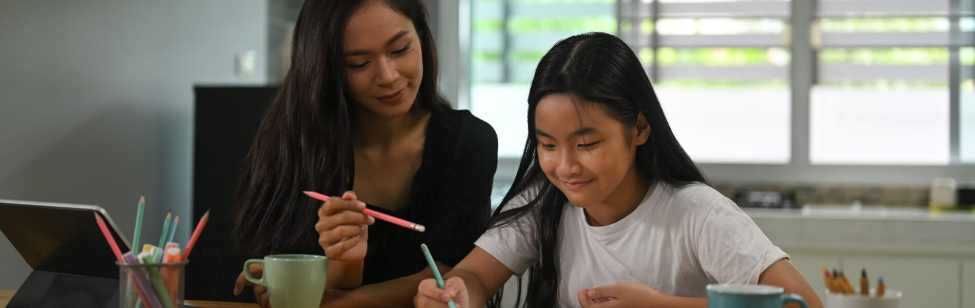 A mother is sitting with her daughter and teaching her homework at the wooden working desk.