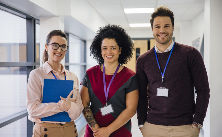 Three teachers standing in a hallway smiling