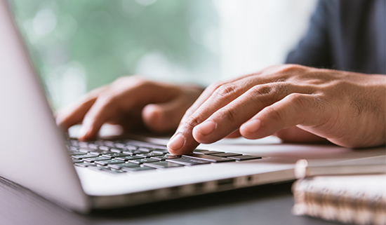 Image of close up of hands operating laptop