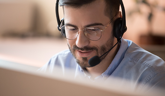 Image of a helpdesk operator taking a call on his headset
