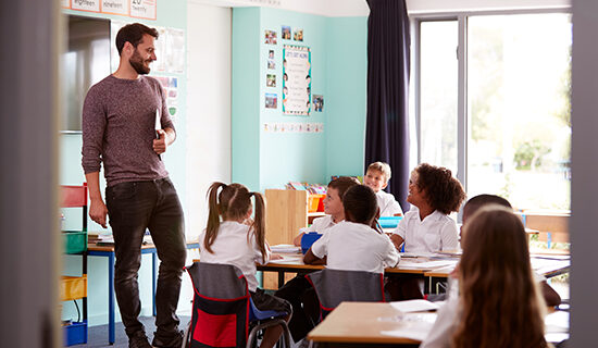 Image of a male teacher smiling in a primary classroom with young children