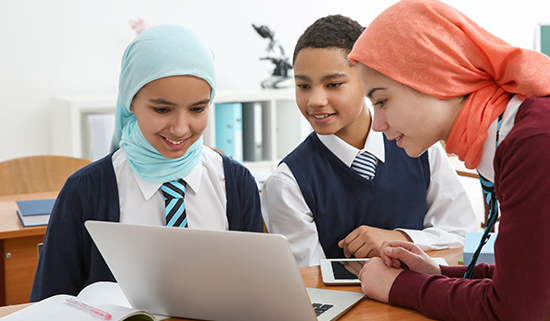 Image of three secondary school aged pupils viewing a laptop