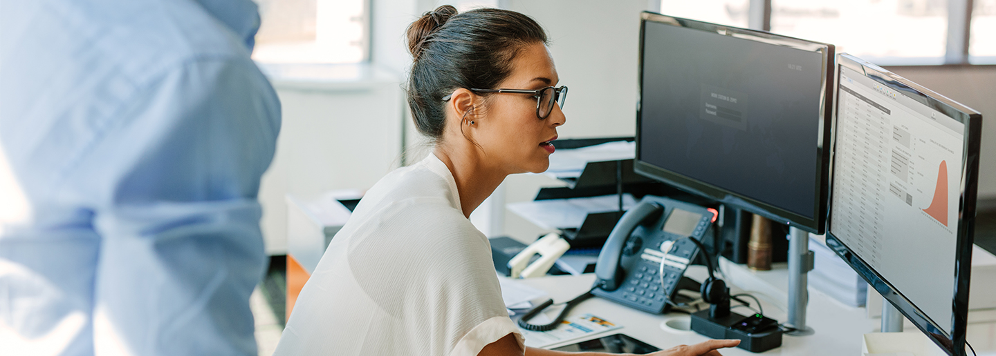 Image of a female business person viewing reports on a computer