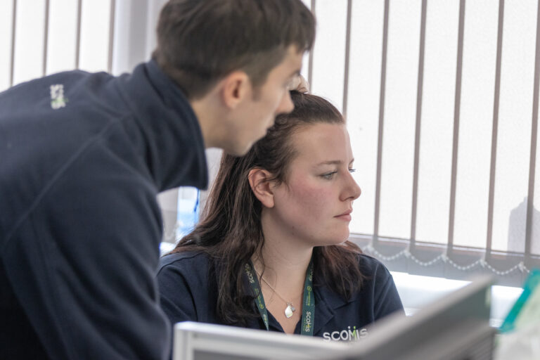 Close up of two Scomis staff members looking at a screen