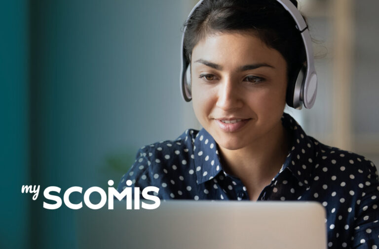 Image of woman working on a laptop to access MyScomis customer portal